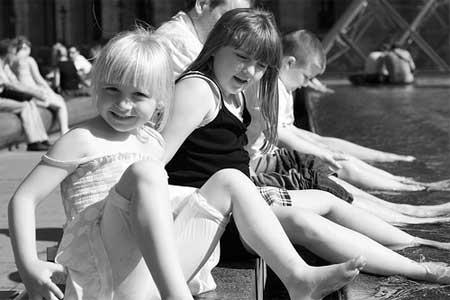 A alegria das meninas brincando na água na fonte do Louvre em Paris